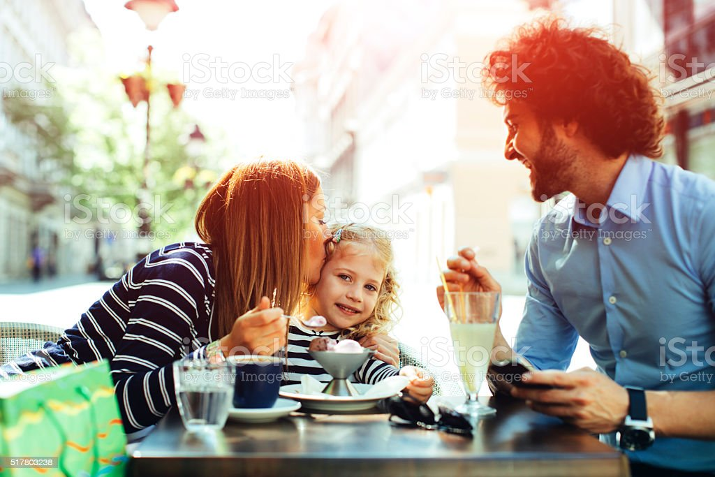 Father And Mother With Their Daughter in Cafe. stock photo