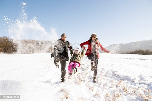 istock Father and mother with their daughter, playing in the snow. 865003508