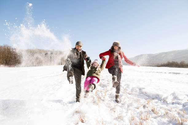 Father and mother with their daughter, playing in the snow. stock photo