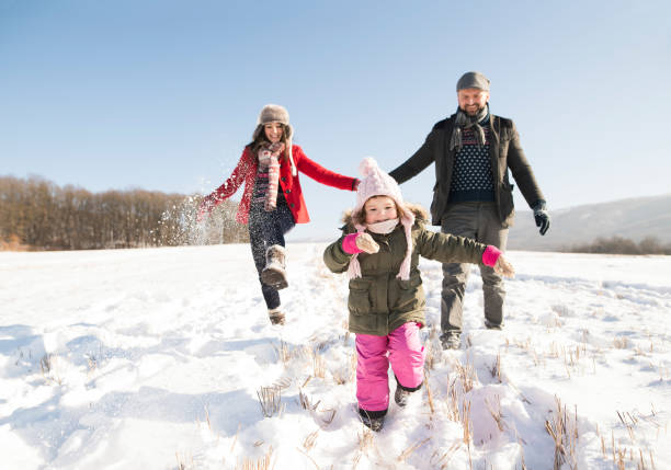 vater und mutter mit ihrer tochter, spielen im schnee. - schneespiele stock-fotos und bilder