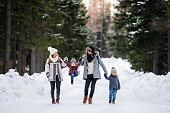 Front view portrait of father and mother with two small children in winter nature, walking in the snow.
