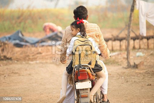 Rural father drives daughter to home from the school on motorbike