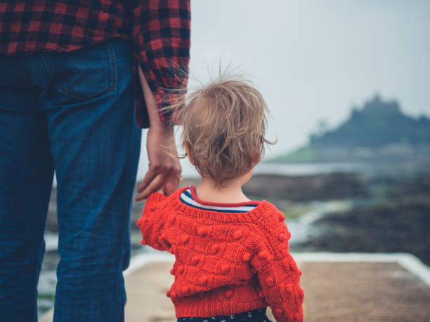 Father and small son on pier by the sea stock photo
