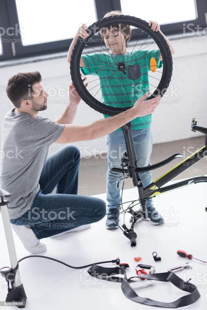 father and son affixing bicycle wheel together on white stock photo