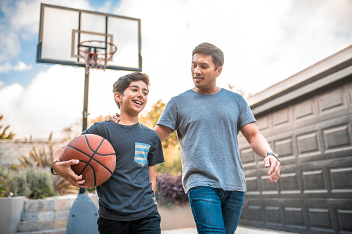 Happy boy after the  basketball match with his father. Mid adult man and child are smiling in backyard. They are wearing casuals during weekend.