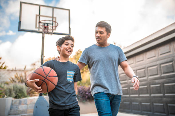 Father and son after the basketball match on back yard Happy boy after the  basketball match with his father. Mid adult man and child are smiling in backyard. They are wearing casuals during weekend. father stock pictures, royalty-free photos & images