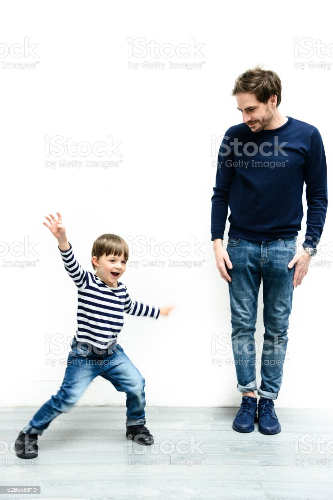 father and son against the white wall stock photo