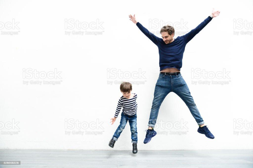 Padre e hijo en contra de la pared blanca - foto de stock