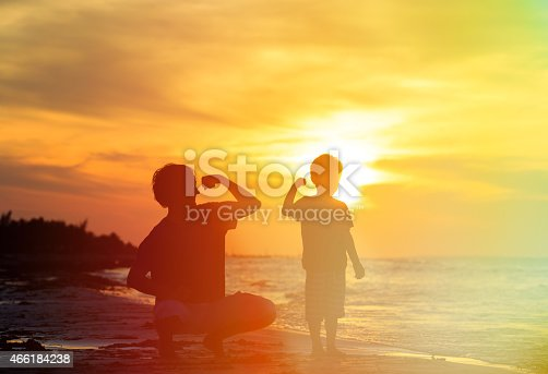 997711042istockphoto Father and son are comparing biceps at sunset 466184238