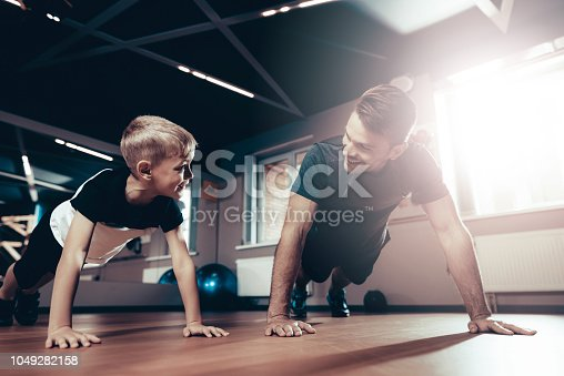 997711042istockphoto Father And Son Are Doing Push Ups In The Gym. 1049282158