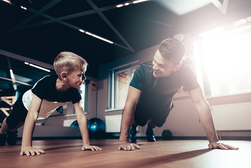 Father And Son Are Doing Push Ups In The Gym. Parenthood Relationship. Sporty Family Concept. Active Lifestyle. Triceps Exercise. Holiday Leisure. Working Out Together. Fitness Day.