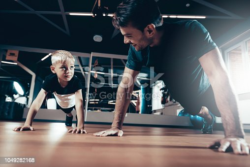 997711042istockphoto Father And Son Are Doing Push Ups In The Gym. 1049282168