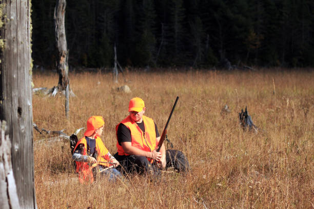 Father and son are hunting Hunters in the autumn forest hunter stock pictures, royalty-free photos & images