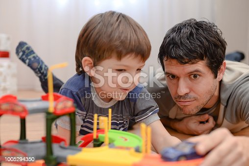 540396126istockphoto Father and son are playing with toy cars 1005294350