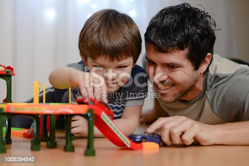 540396126istockphoto Father and son are playing with toy cars 1005294542