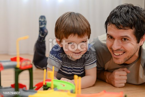 540396126istockphoto Father and son are playing with toy cars 1005294602