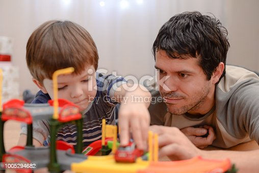 540396126istockphoto Father and son are playing with toy cars 1005294682