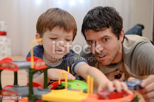 540396126istockphoto Father and son are playing with toy cars 1005294716