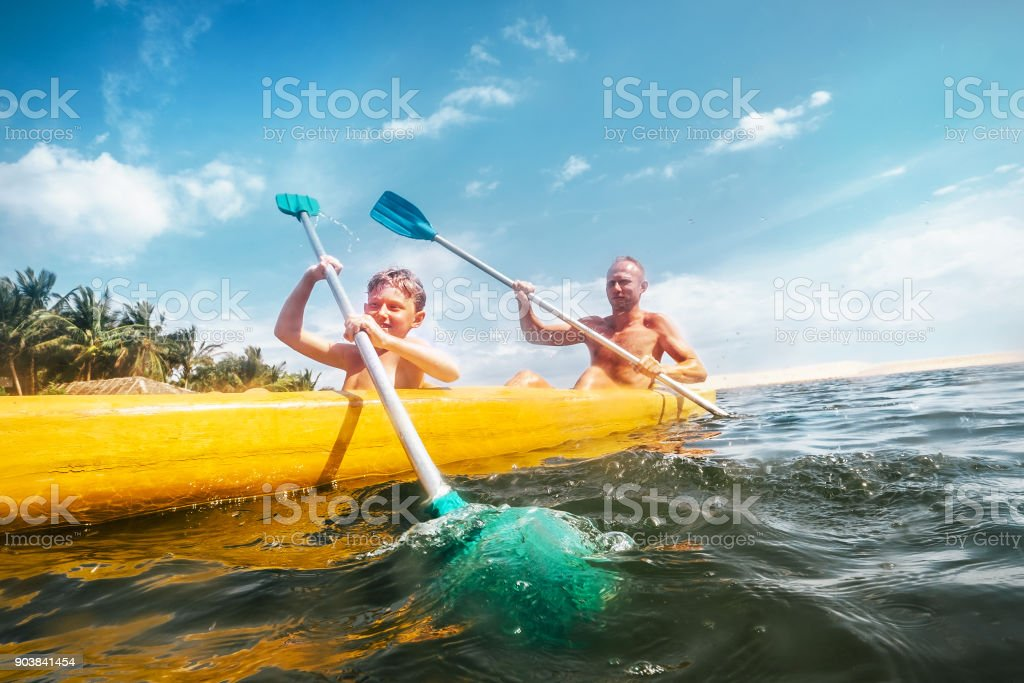 Father and son are sailing in the canoe stock photo