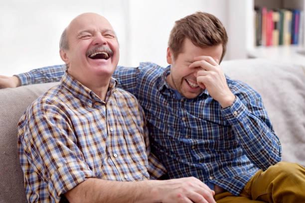 vater und sohn auf dem sofa im wohnzimmer sitzen und erinnere mich an witz - papa humor stock-fotos und bilder