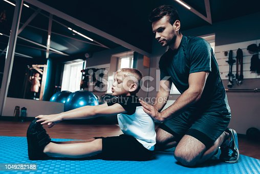 997711042istockphoto Father And Son Are Stretching Each Other In Gym. 1049282188