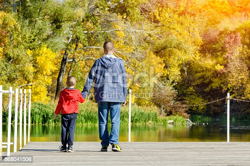 Father and son are walking along the pier. Autumn, sunny. Back view