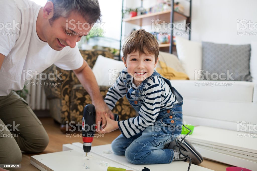 Father and son assembling furniture royalty-free stock photo