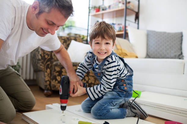 Father and son assembling furniture stock photo