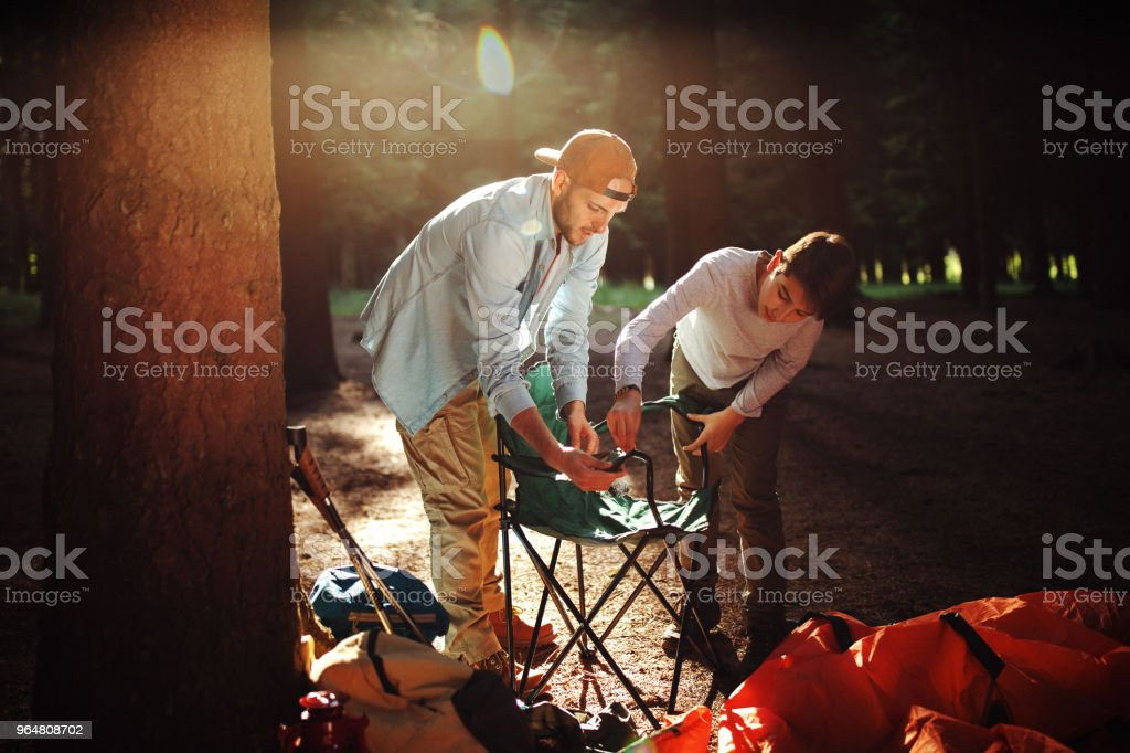 Father and son assembling the chair in forest for camping royalty-free stock photo