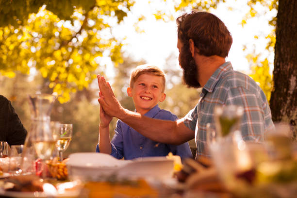 Father and son at a family picnic in nature - high five stock photo