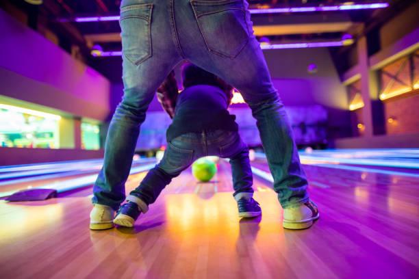 vader en zoon op bowlingbaan - bowlen stockfoto's en -beelden