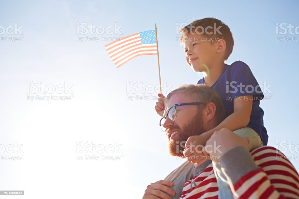 Father and son at parade Patriotic family with American flag visiting parade devoted to Independence Day Adult Stock Photo