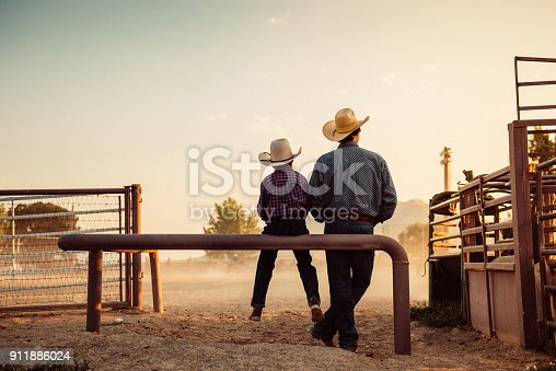 Father and son sitting by rodeo arena at sunrise