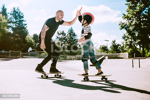 A fun, playful Hispanic Dad and his son play together at a skate park. The boy has a helmet and padding, and is having fun with his father. They give each other a high five.  A depiction of a loving supportive dad.