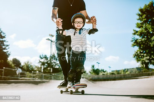 A fun, playful Hispanic Dad and his son play together at a skate park. The boy has a helmet and padding, and is having fun with his father. The father smiles as he teaches his young boy skateboarding, holding him for balance.  A depiction of a loving supportive dad.