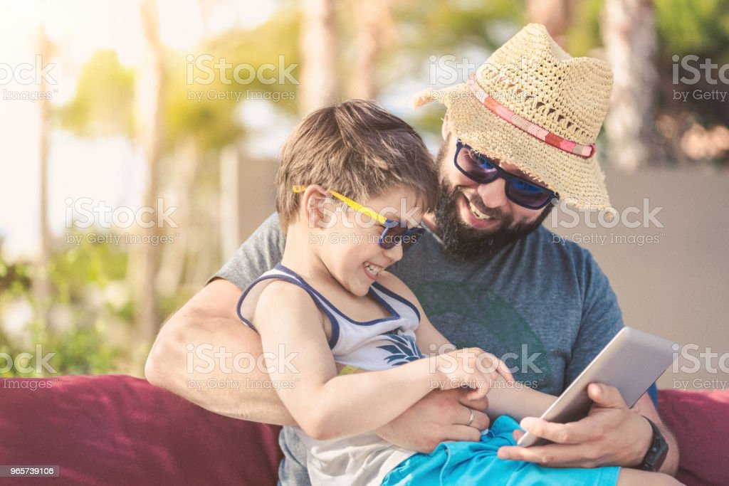 Father and son at sunset with digital tablet on vacation - Royalty-free Beach Stock Photo