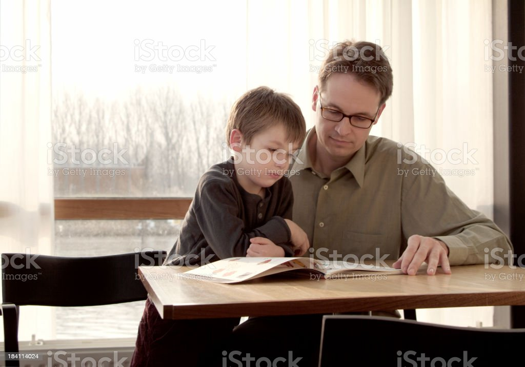 A father and son at table reading a magazine together royalty-free stock photo