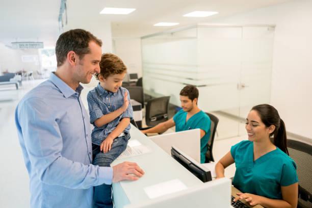 vater und sohn im krankenhaus - bürorezeption stock-fotos und bilder