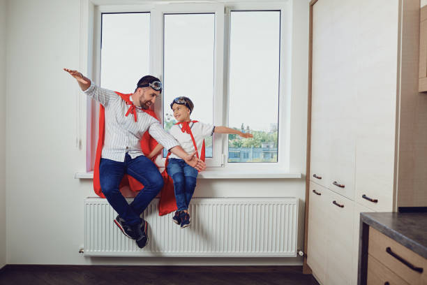 father and son at the window in the room - fathers day stock photos and pictures