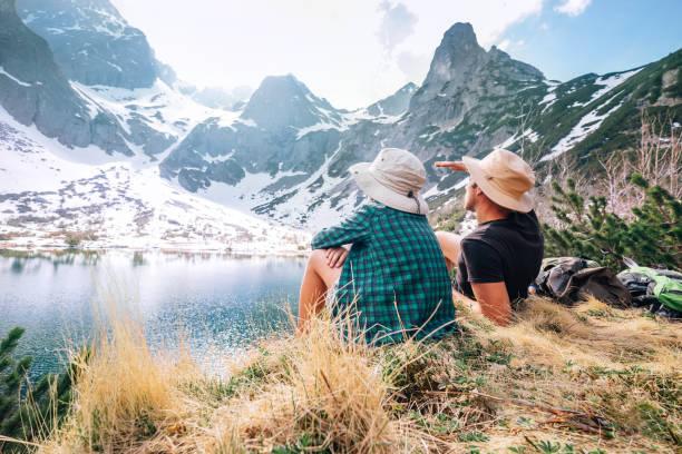 아버지와 아들 배낭 산 호수 근처 앉아서 눈 덮인 산봉우리를 즐길 수 - 슬로바키아 뉴스 사진 이미지