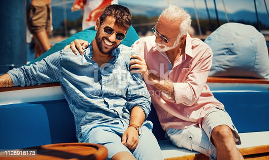 Father and son sitting on the yacht having a relaxed conversation and enjoying sailing.