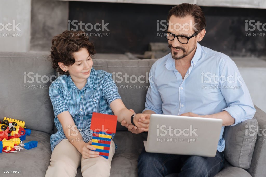 Father and son bonding to each other on the sofa stock photo