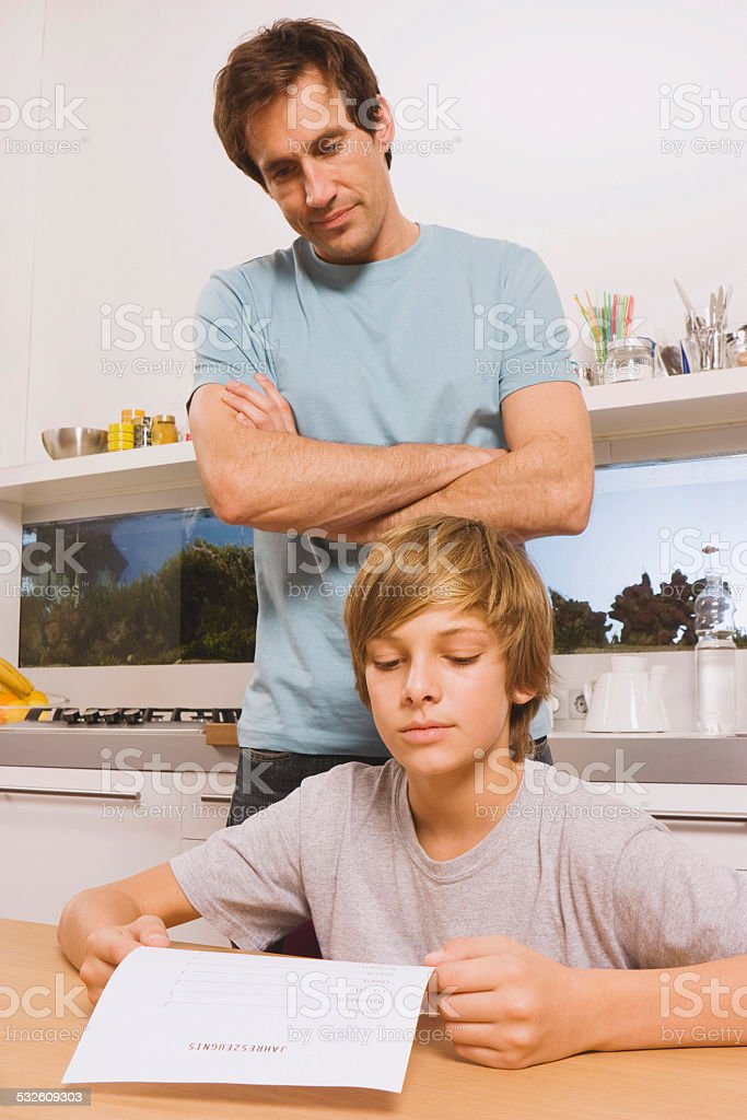 Father and son boy with report card man watching stock photo