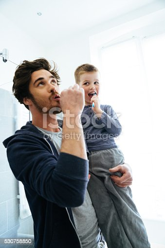 185211538istockphoto Father And Son Brushing Teeth 530758850