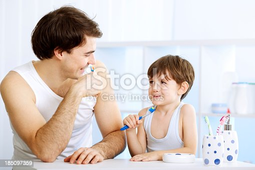 185211538istockphoto Father and son brushing teeth together. 185097359