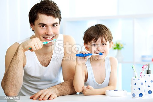 185211538istockphoto Father and son brushing teeth together. 185207589