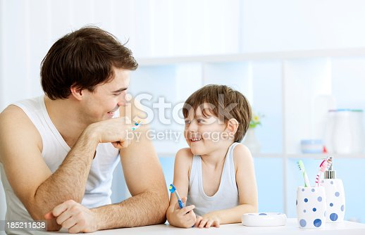 185211538istockphoto Father and son brushing teeth together. 185211538