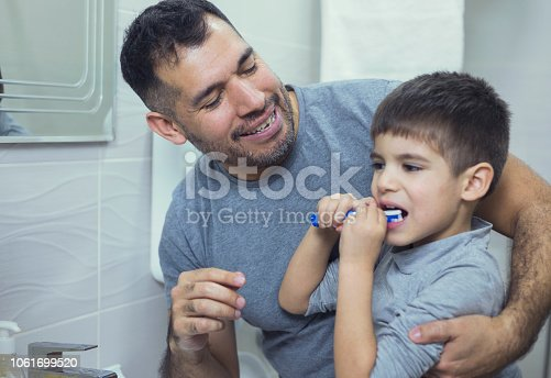 Father teaching son how to brash his teeth correctly