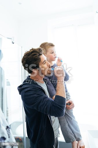 185211538istockphoto Father And Son Brushing Their Teeth 598232674
