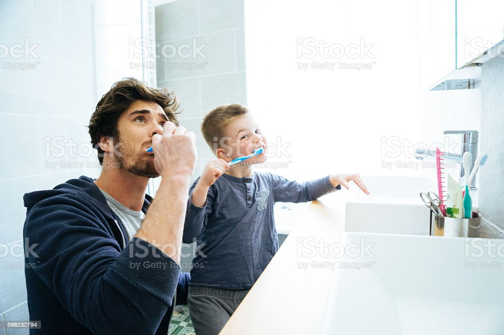 Father And Son Brushing Their Teeth stock photo